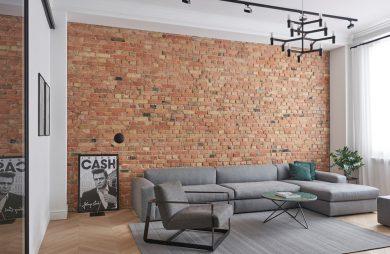 salon w apartamencie szarymi meblami do siedzenia na tle ceglanej ściany