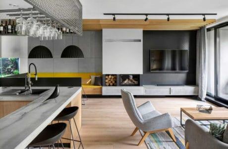 nowoczesne wnętrze domu z jasną podłogą oraz białymi meblami i szarym wygodnym fotelem