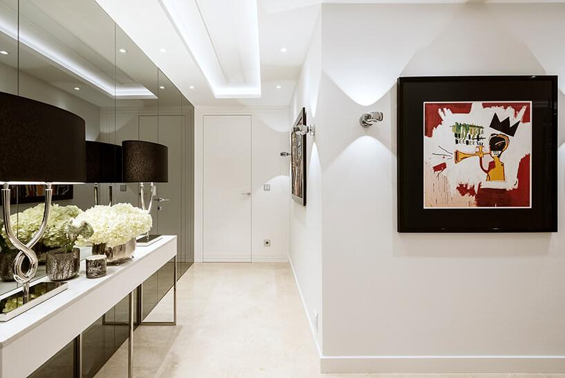 biały hol ze szklaną ciemną ścianą jako tło dla białej szafki zeleganckim czarnymi lampami