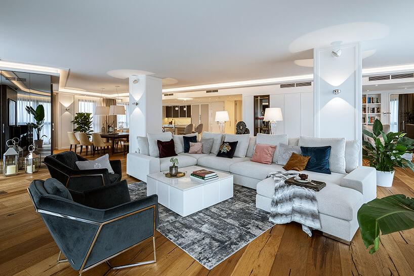elegancki jasny salon zbrązową drewnianą podłogą pod dużą białą narożną sofą idwoma eleganckim ciemnymi fotelami