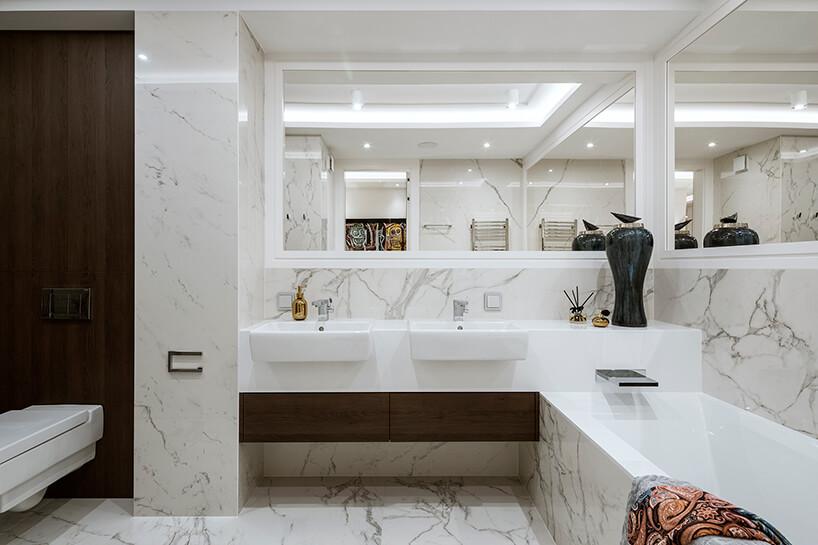 elegancka łazienka zbiałego kamienia zdużymi lustrami na ścianach