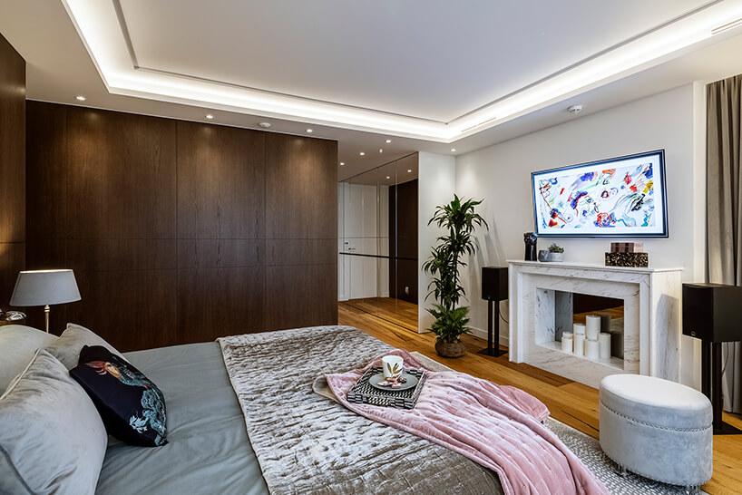sypialnia zdrewnianą podłogą zkominkiem zabudowanym białym kamieniem