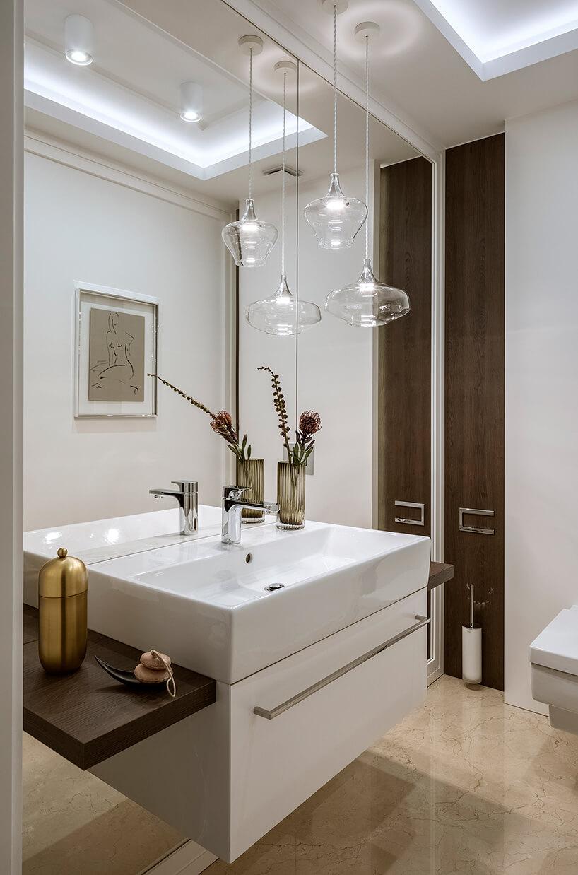 jasna łazienka zlustrem na całej ścianie zpodwieszoną umywalką zkamienną podłogą