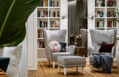 dwa eleganckie srebrne fotele przy dwóch podnóżkach na drewnianej podłodze na tle białych półek