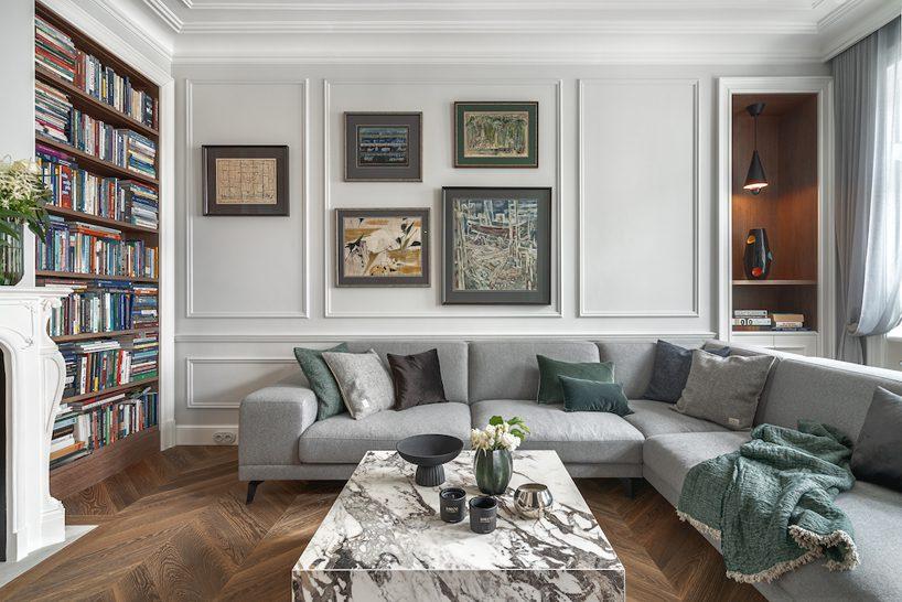 apartament od whitecastle na mokotowskiej biały salon zciemną drewnianą podłogą iszafą narożną sofą