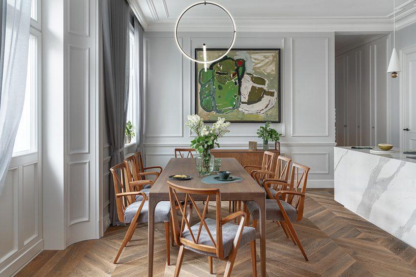 apartament wstylu paryskim zmeblami od Nobonobo duży drewniany ciemny stół zdrewnianymi krzesłami