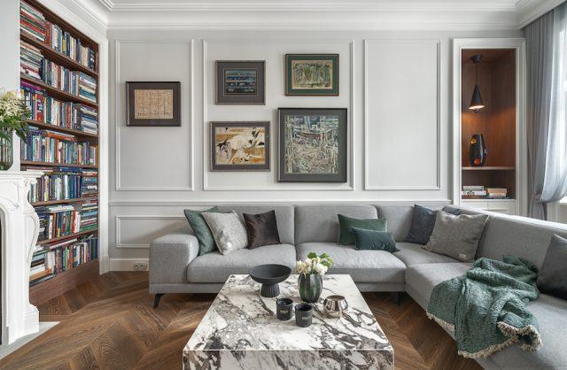 apartament od whitecastle na mokotowskiej biały salon z ciemną drewnianą podłogą i szafą narożną sofą