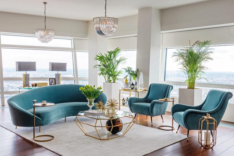 niebieska kanapa ifotel stolik wkrztałcie diamentu na tle białych ścian