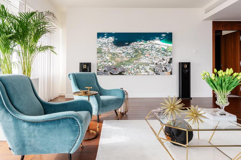 niebieskie fotele stolik wkrztałcie diamenut głosniki na tle białej ściany zobrazem
