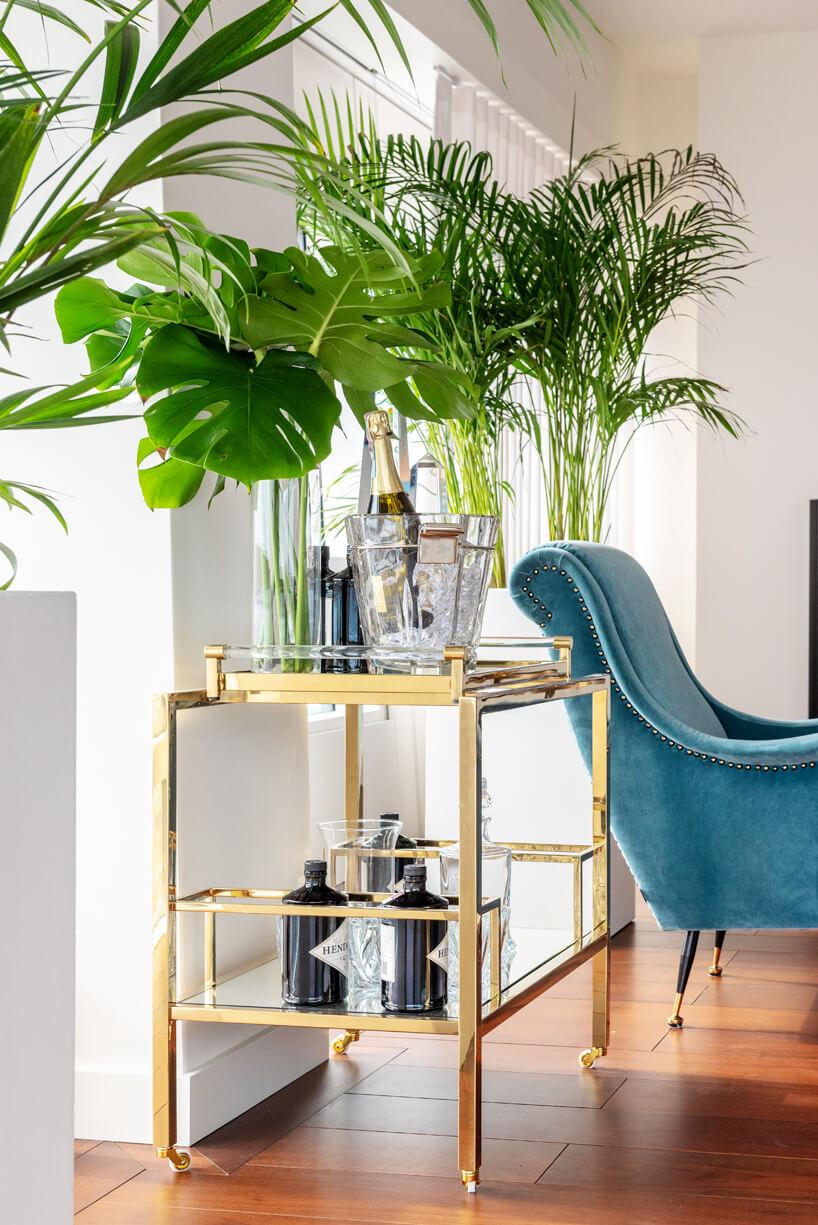 niebieski fotel istolik zkwiatami na tle białej ściany