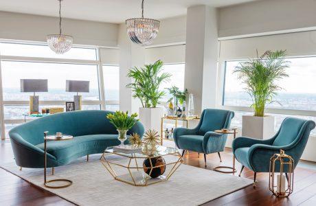 niebieska kanapa i fotel stolik w krztałcie diamentu na tle białych ścian