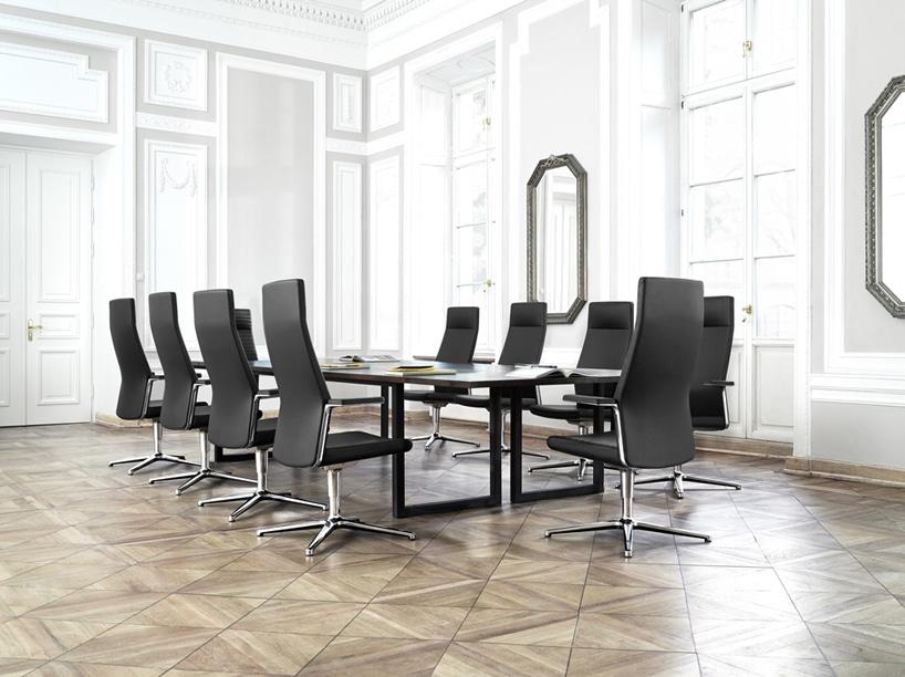 biała sala konferencyjna zdrewnianą podłogą zczarnym stołem zeleganckimi czarnymi fotelami