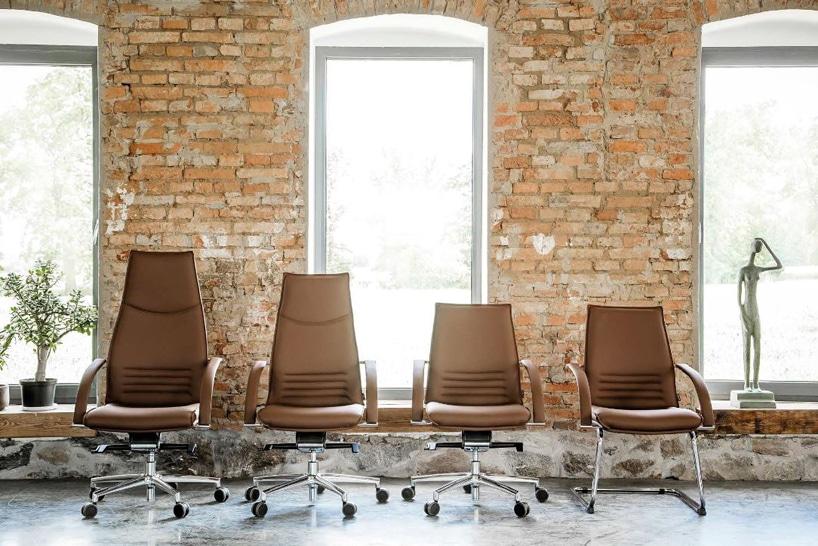 cztery brązowe krzesła na tle ceglanej ściany