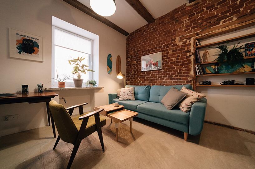projekt kawalerki od MRSatelier niebieska sofa na krótkcih drewnianych nogach na tle ceglanej ściany