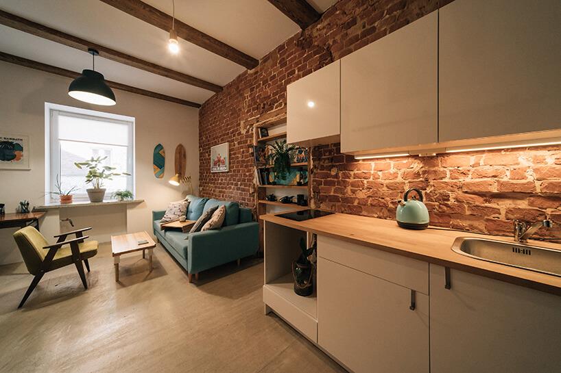 projekt kawalerki od MRSatelier aneks kuchenny zbiałymi szafkami idrewnianym blatem na tle ceglanej ściany