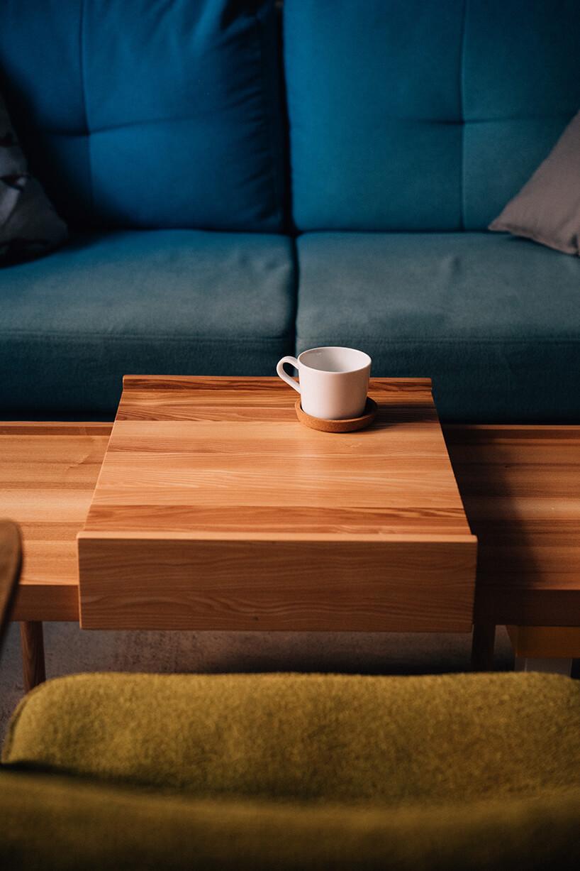 projekt kawalerki od MRSatelier zmęczone zielone siedzisko fotela 366 przy małym drewnianym stoliku znakładką