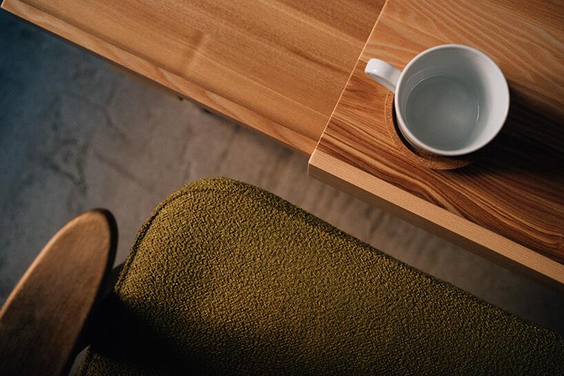 projekt kawalerki od MRSatelier stare zielone siedzisko ioparcie fotela 366 przy drewnianym blacie stolika zbiałym kubkiem