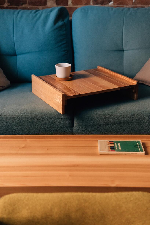 obdrapana pusta kawalerka ze starym drewnianym otwartym zakratowanym oknem drewniana nakłądka ze stolika na niebieskiej sofie