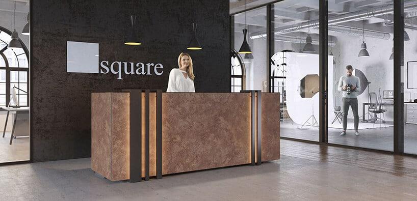 kamienne czerwonawe biurko zmetalowymi pionowymi pasami na tle czarnej ściany zlogo