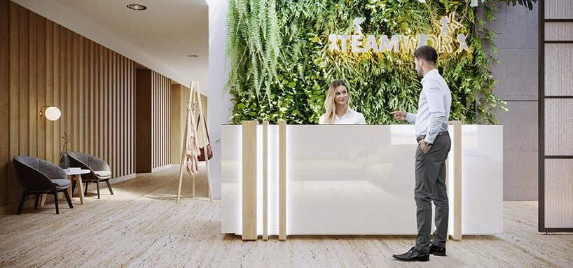 białe połyskujące recepcyjne biurku zmetalowymi dodatkami na tle ściany pokrytą roślinami oraz świecącym neonem