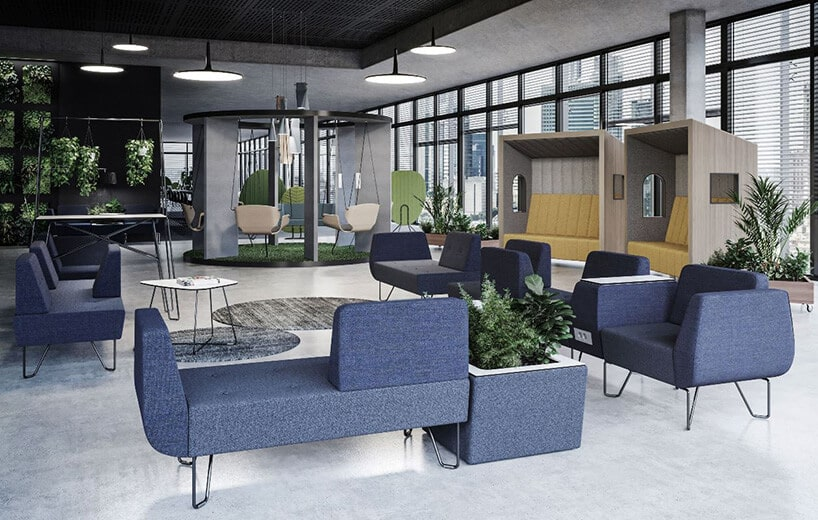 wnętrze nowoczesnej poczekalni zgeometrycznymi niebieskim kanapami dużą ilością zielonych roślin oraz boxami do indywidualnej pracy