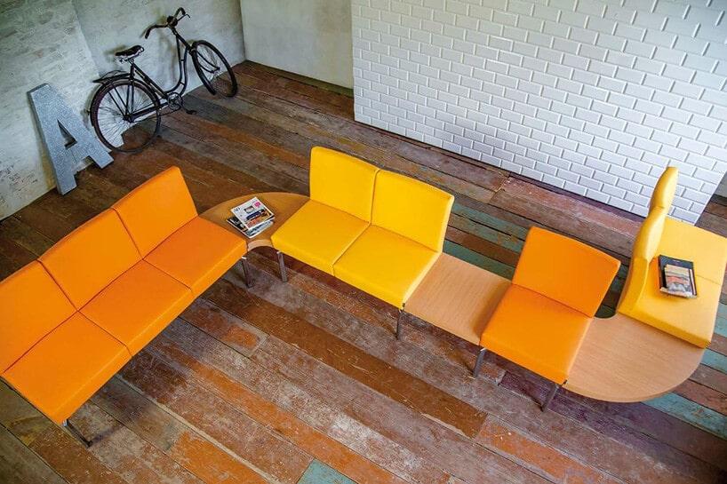 podniszczone drewniane deski na podłodze wpomieszczeniu zbiałą licówką oraz kanapą wliterę Soraz kolorze pomarańczowym