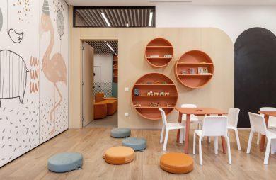 aranżacja przedszkola projektu Svoya Studio na Ukrainie sala zabaw z drewnianą podłogą z biała ścianą z narysowanymi zwierzętami z małymi pomarańczowymi stolikami i białym krzesełkami