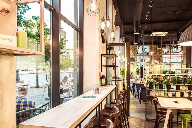 wnętrze restauracji wdzień zwysokim stołem przy oknie