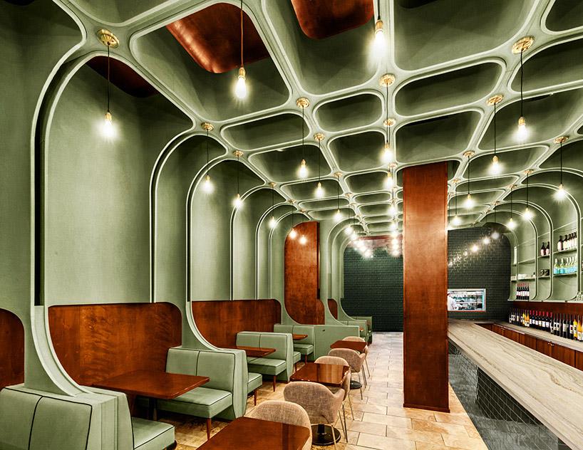 restauracja wkolorze zielonym zciemnymi drewnianymi wykończeniami