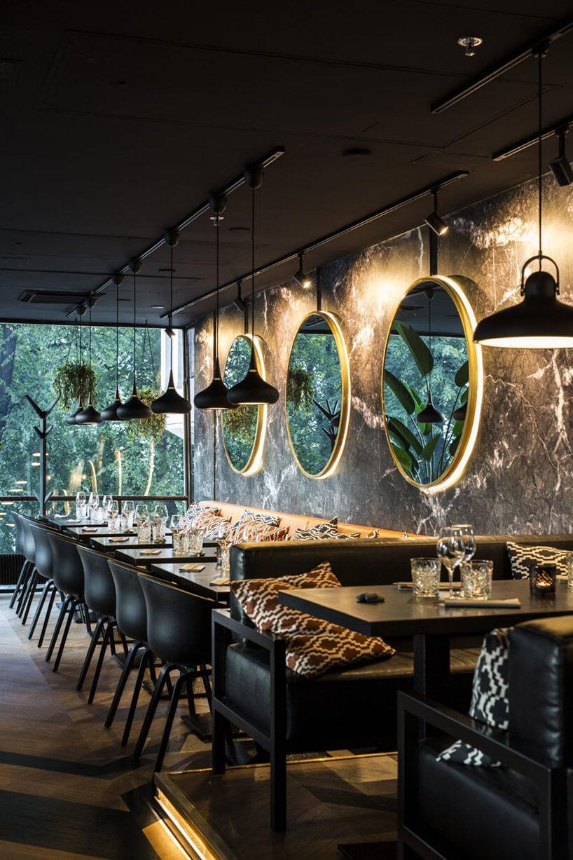 wnętrze restauracji zpodświetlonymi lustrami na ścianie