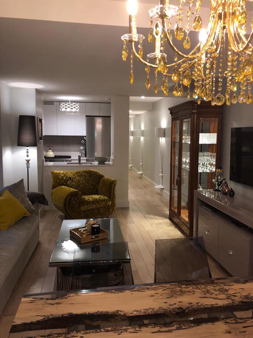 wnętrze salony połączonego zaneksem kuchennym zduzym żółtym fotelem