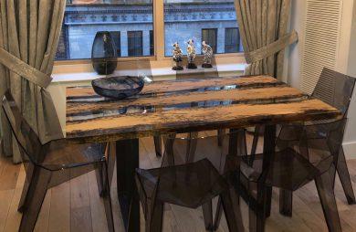 duży stół ze szklano-drewnianym blatem i przeźroczystymi ciemnymi krzesłami