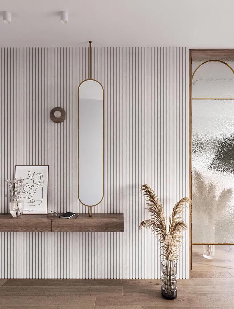 przedpokój zwąskim zaokrąglanym lustrem zamocowanym na rurze do sufitu wciemnym fornirze ipółki