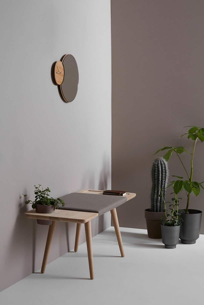 minimalistyczne wnętrze wjasnym różu iciemnym brązie zdrewnianym stolikiem oraz roślinami