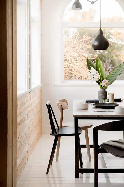 stół zczarną ramą jasnym blatem drewnianym oraz czarnymi ijasno drewnianymi krzesłami