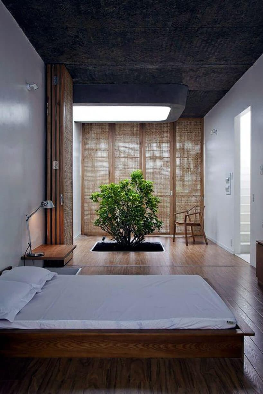 wysoka sypialnia zzparawanem oraz wyciętą dziurą zziemią zzielonym drzewkiem