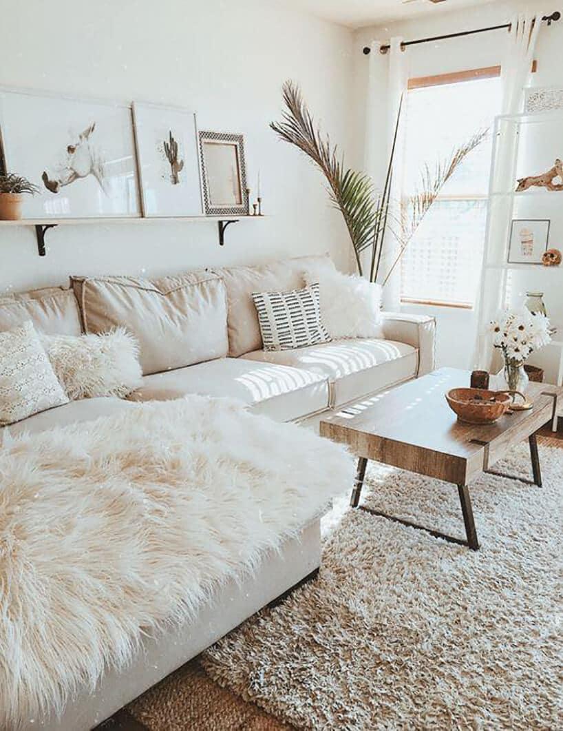 salon zdużą wygodną kanapą wjasnym beżu zbiałym futerkiem obok wysokich liści palmowych przy oknie