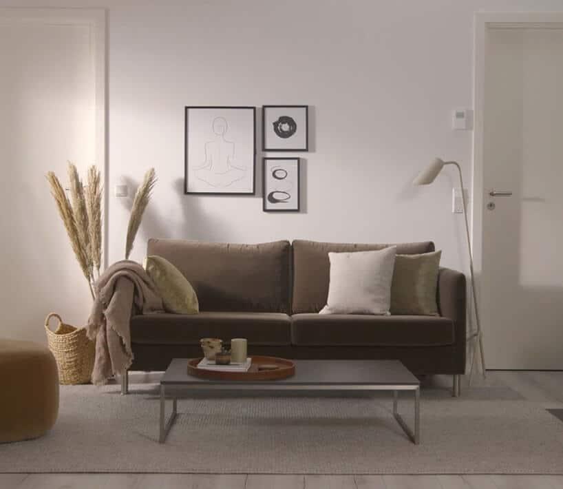 prosta wąska kanapa wciemnej tonacji przy białej ścianie ztrzema obrazkami idodatkami wokół