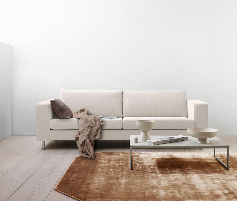 biała kanapa wprostokącie przy kawowym stoliku zchromowanymi nogami na dywanie wkawie zmlekiem