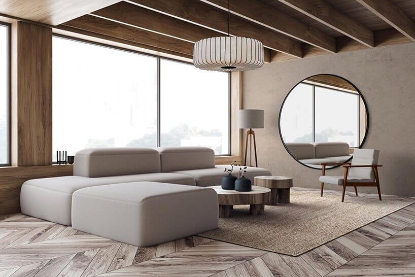 minimalistyczna przestrzeń zprostą bryłą szarej kanapy przy lampie na trójnogu