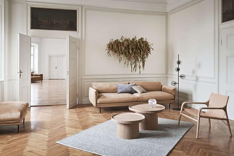 duże wnętrze ze zdobieniami ściennymi oraz ciepłymi tkaninami mebli oraz szarym dywanie zfakturą