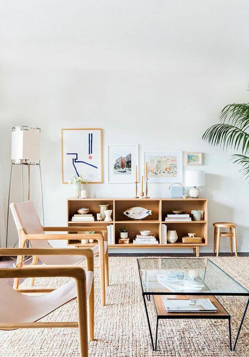 szklany stolik kawowy zczarną ramą obok drewnianych krzeseł zróżowym materiałem przy otwartej komodzie zpółkami