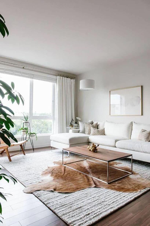 doświetlone wnętrze dużym białym oknem wsalonie zjasną kanapą oraz drewnianym stolikiem kawowym
