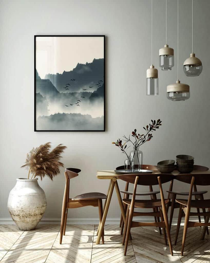 szara ściana zobrazem wczarnej ramie wjadalni zretro stołem