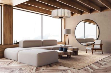 minimalistyczna przestrzeń z prostą bryłą szarej kanapy przy lampie na trójnogu