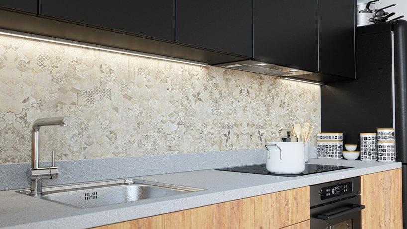 Czarne meble kuchenne zjasną wzorzystą ścianą.