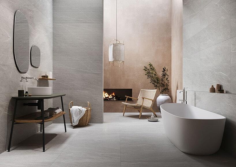 salon kąpielowy zkaflami zfakturą oraz dodatkiem beżowego iczarnego kominka