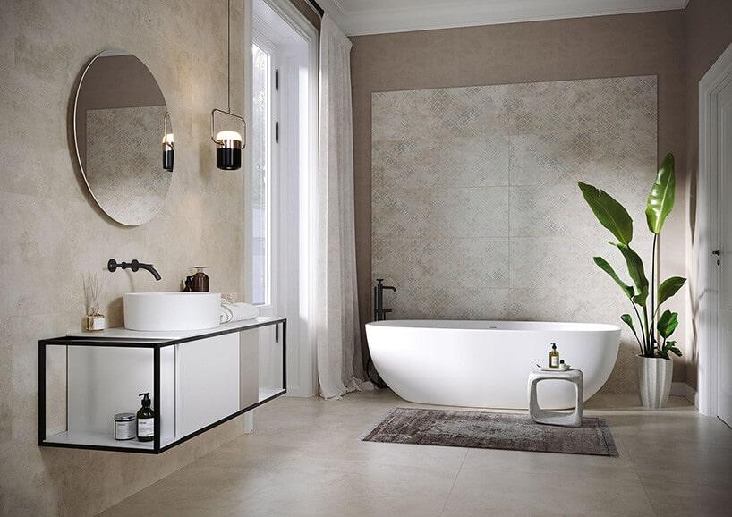 duża łazienka zpodwieszaną szafką zczarną ramą oraz wolnostojąca wanna obok zielonej roślinie