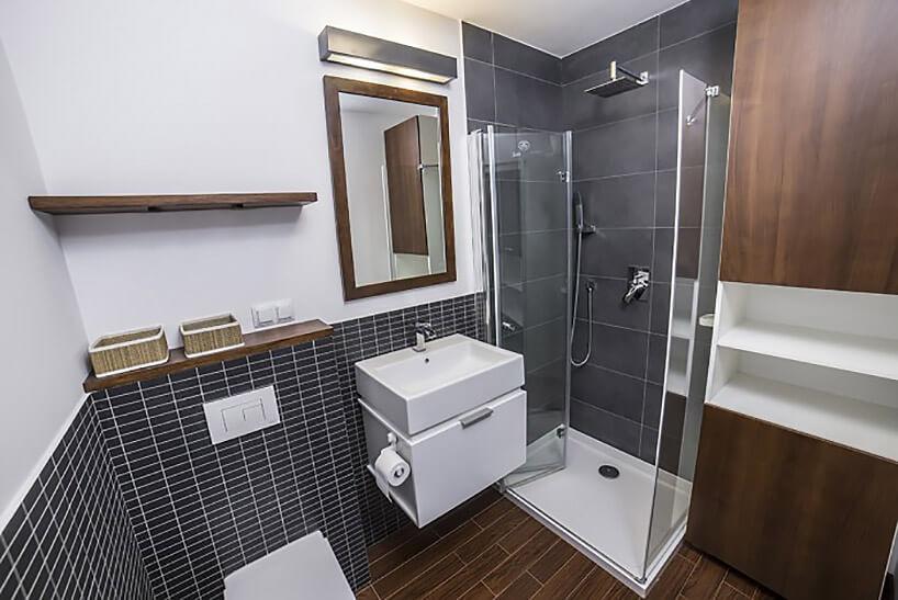 mała łazienka zszarymi płytkami idrewnianymi wstawkami