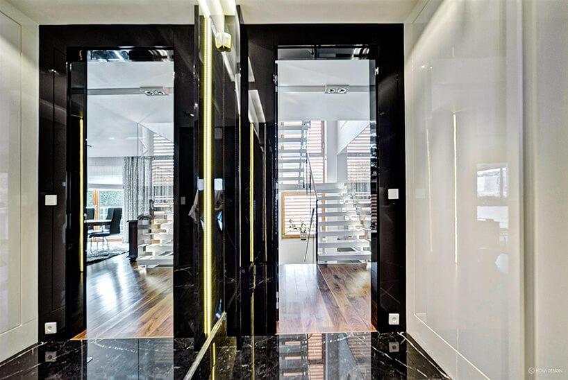 korytarz zdużym lustrem iczarnymi drzwiami do pokoju